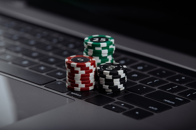 Żetony do pokera na laptopie. koncepcja kasyna online.