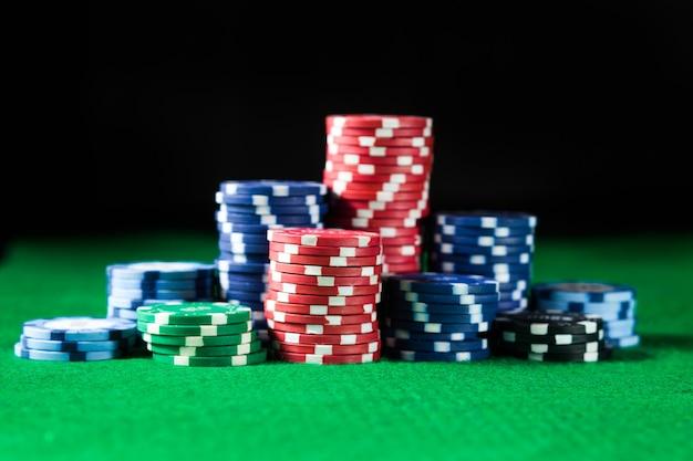 Żetony do pokera w kasynie na zielonej powierzchni stołu. hazard, fortuna