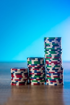 Żetony do pokera w stosie na niebieskim tle