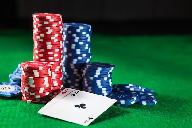 Żetony do pokera z dwoma kartami asów na zielonym stole na czarnej powierzchni