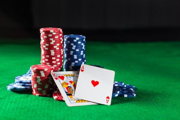 Żetony do pokera z dwoma kartami, królem i ace na zielonej powierzchni.
