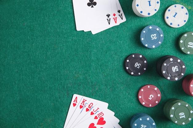 Żetony i karty w kasynie na zielonym stole.