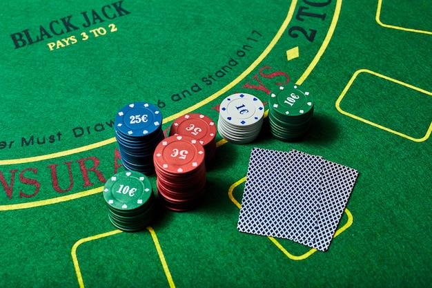 Żetony kasyna i talia kart leżących na zielonym stole w kasynie, koncepcja gry w pokera.