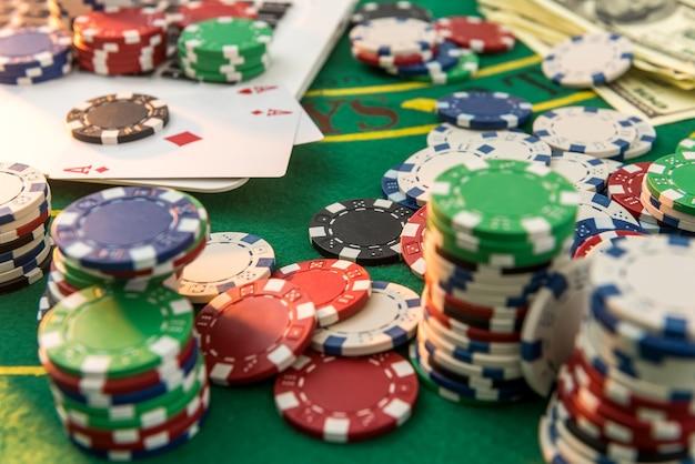 Żetony, pieniądze z kart i laptop do pokera online lub hazardu w kasynie. ryzyko dla wygranych pieniędzy.