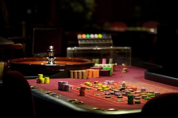 Żetony z bliska i ruletka w kasynie na czerwonym stole
