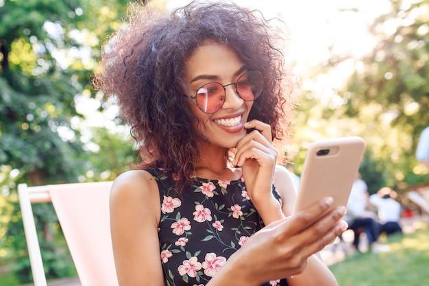 Zewnątrz bliska portret uśmiechnięta czarna kobieta za pomocą telefonu komórkowego i dokonywania autoportretu