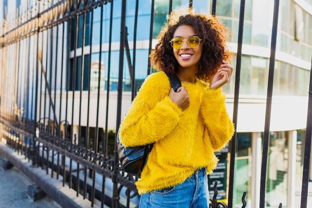 Zewnątrz jasny portret szczęśliwa dziewczyna z plecakiem i stojąc na miejskich