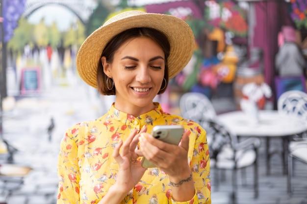 Zewnątrz moda portret kobiety w żółtej letniej sukience na kolorowej ścianie ulicy