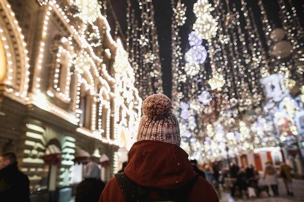 Zewnątrz nocny portret młodej kobiety modnej w czapka zimowa z pomponem widok z tyłu. efekt magicznego śniegu. nocne oświetlenie uliczne w moskwie.