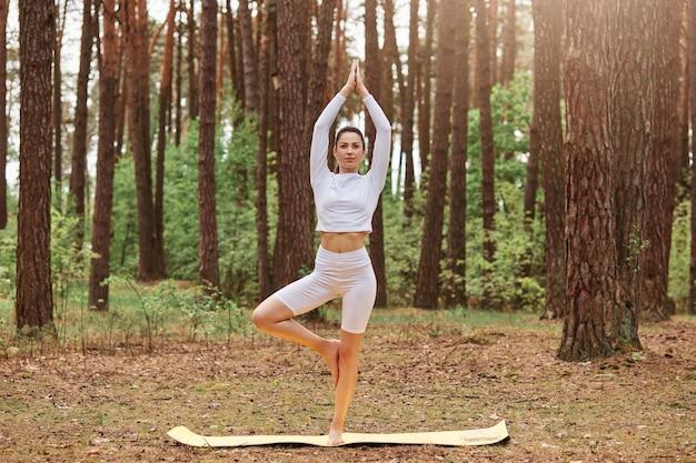 Zewnątrz pełnej długości portret sportowy kobiety stojącej na jednej nodze i wyciągając ręce w górę, ściskając dłonie razem, kobieta w pozie jogi drzewa, ćwicząc w lesie.