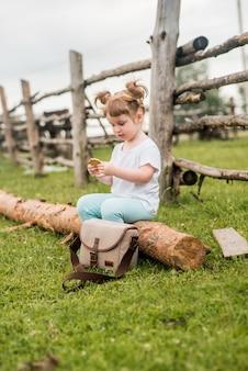 Zewnątrz pionowy portret dziewczyny siedzącej na trawie w pobliżu ogrodzenia. lato we wsi. piękna dziewczynka na drewnianej ławce. ekologia i szczęśliwe dzieciństwo.