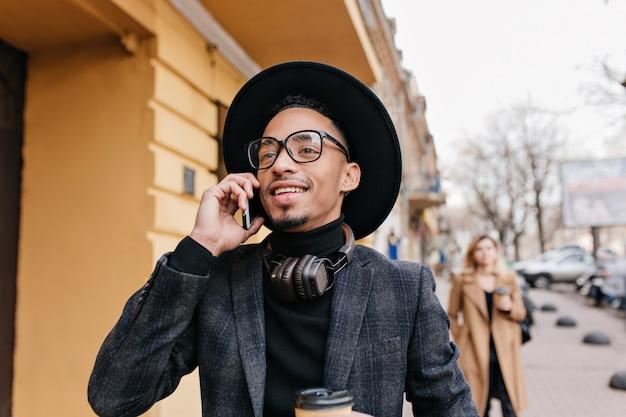 Zewnątrz portret brunetki mężczyzna rozmawia przez telefon i marzycielski odwracając. zdjęcie ruchliwego uśmiechniętego afrykańskiego chłopca dzwoniącego do kogoś na ulicy miasta.