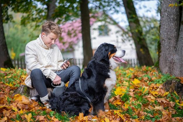 Zewnątrz portret chłopca z berneńskim psem jesienią. przyjaźń nastolatka ze zwierzakiem.