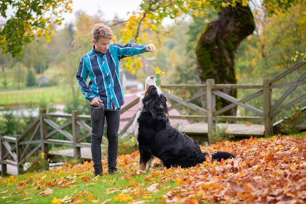 Zewnątrz portret chłopca z berneńskim psem pasterskim. przyjaźń nastolatka ze zwierzakiem, chłopiec spacerujący w jesiennym parku