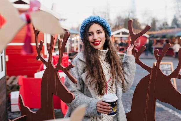 Zewnątrz portret długowłosej dziewczyny z filiżanką kawy, pozowanie w pobliżu zabawek jeleni w zimowe wakacje. zdjęcie uroczej kobiety w niebieskim kapeluszu stojącej obok świątecznych dekoracji w parku.