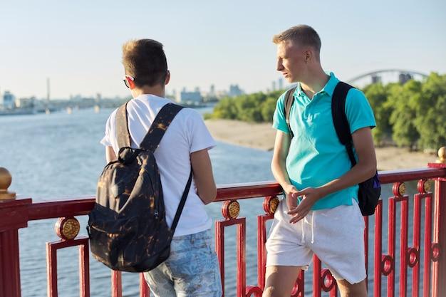 Zewnątrz portret dwóch przyjaciół chłopcy nastolatki 15, 16 lat, rozmawiając, śmiejąc się. faceci stojący na moście nad rzeką w słoneczny letni dzień. młodzież, przyjaźń, komunikacja
