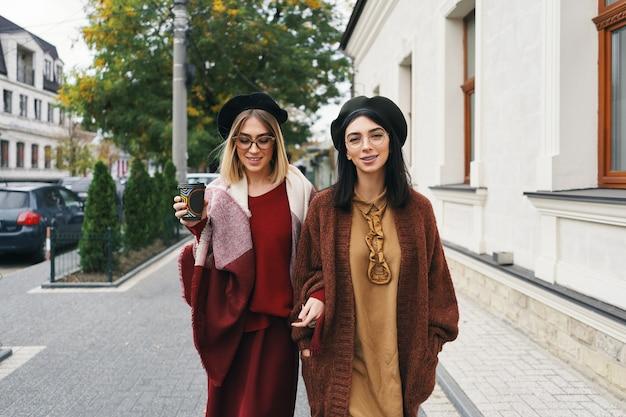 Zewnątrz portret dwóch przyjaciółek. dziewczyny w zwykłych, ciepłych strojach i okularach spacerujące po mieście w zimnych porach roku i bawiące się na miejskiej ulicy. miejski styl życia, koncepcja przyjaźni.