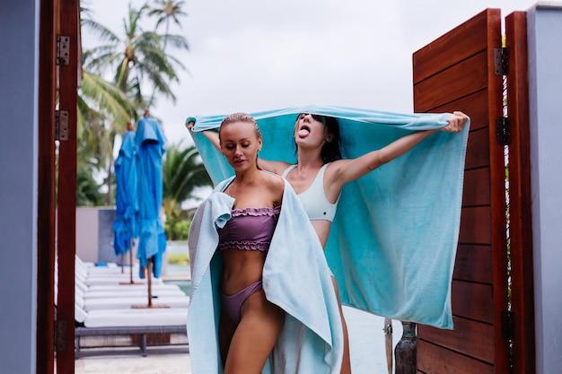 Zewnątrz portret dwóch szczęśliwych kobiet w bikini z ręcznikami plażowymi na wakacjach poza willą przy basenie w deszczowy dzień