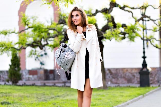 Zewnątrz portret eleganckiej kobiety spacerującej w centrum europy, zabawy i uśmiechnięta, ubrana w beżowy płaszcz i sukienkę glamour, nastrój hipster, wakacje w podróży, czas jesieni.