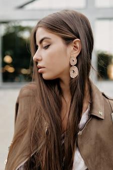Zewnątrz portret eleganckiej, stylowej, pięknej kobiety z długimi włosami ze stawianiem pięknej biżuterii