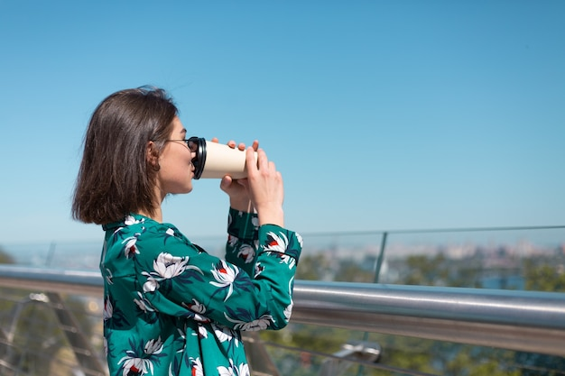 Zewnątrz portret kobiety w zielonej koszuli z filiżanką kawy ciesząc się słońcem, stoi na moście z niesamowitym widokiem na miasto rano