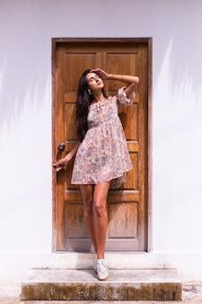 Zewnątrz portret ładnej kobiety z długimi włosami stojącymi przy drewnianych brązowych drzwiach, ubrana w uroczą letnią sukienkę,