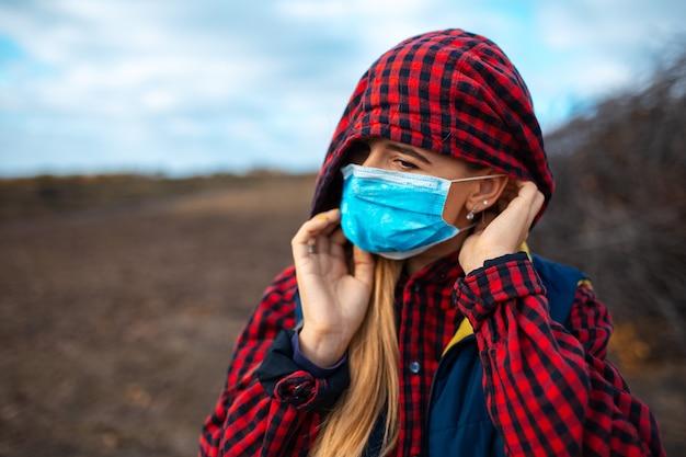 Zewnątrz portret młodej dziewczyny z kapturem w masce medycznej przeciwko koronawirusowi