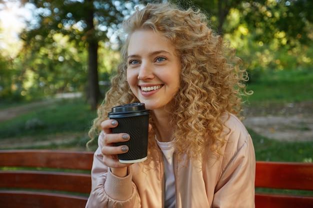 Zewnątrz portret młodej pięknej kobiety blondynka siedzi na ławce w parku, pijąc kawę