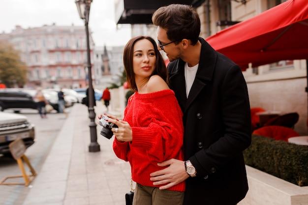 Zewnątrz portret modnej eleganckiej pary zakochanych spaceru po ulicy podczas randki lub wakacji. brunetka dama w czerwonym swetrze robienie zdjęć aparatem.