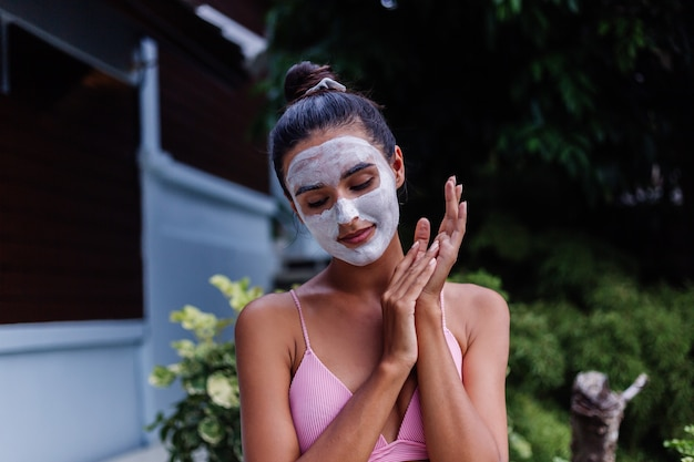 Zewnątrz portret opalonej skóry spokojny dość kaukaski kobieta w bikini w spa z białą maską peeling na twarzy