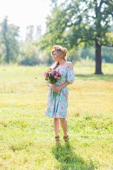 Zewnątrz portret pięknej kobiety blondynka. atrakcyjna szczęśliwa dziewczyna w polu z bukietem kwiatów.