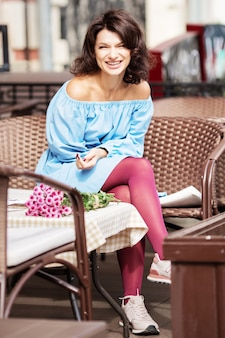 Zewnątrz portret pięknej kobiety przy stole w kawiarni ulicy miasta.