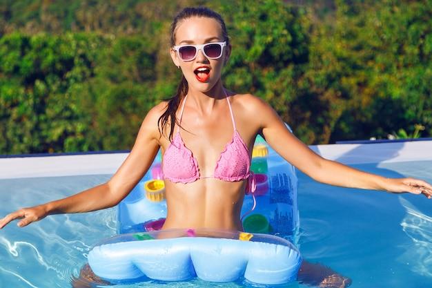 Zewnątrz portret pięknej młodej kobiety zabawy w basenie bez krawędzi z niesamowitym widokiem