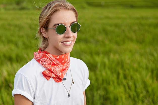 Zewnątrz portret pięknej uśmiechniętej kobiety ubranej w casualową koszulkę i nosi okulary przeciwsłoneczne, stoi na zielonej trawie, spacery