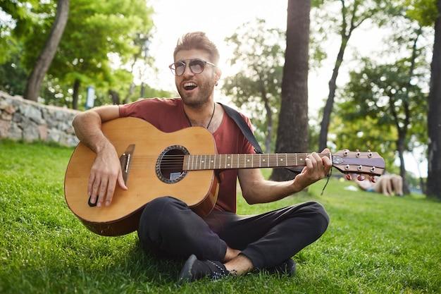 Zewnątrz portret przystojny beztroski hipster facet siedzi na trawie w parku i gra na gitarze