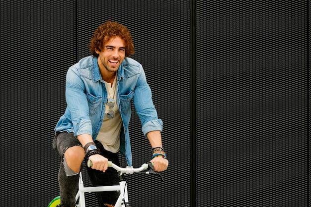 Zewnątrz portret przystojny młody człowiek z rowerem na ulicy.