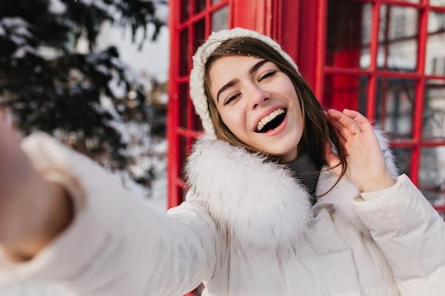 Zewnątrz portret śliczna kobieta z szczęśliwym uśmiechem dokonywanie selfie w londynie podczas ferii zimowych. urocza kobieta w białym kapeluszu, robiąca zdjęcie swojej nogi obok czerwonej budki telefonicznej.