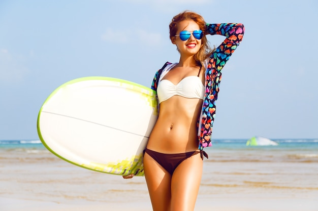 Zewnątrz portret surfer dziewczyna pozowanie na plaży i trzymając deskę surfingową