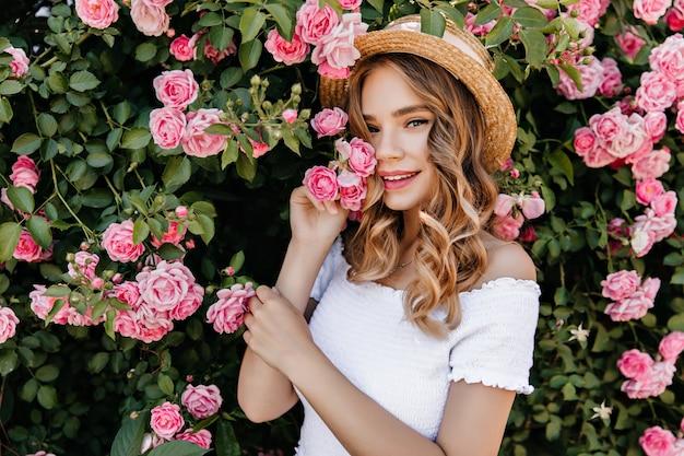 Zewnątrz portret szczęśliwy biała dziewczyna pozuje na charakter. zdjęcie zrelaksowanej kobiety z falującymi włosami stojącej w pobliżu pięknego krzewu różanego.