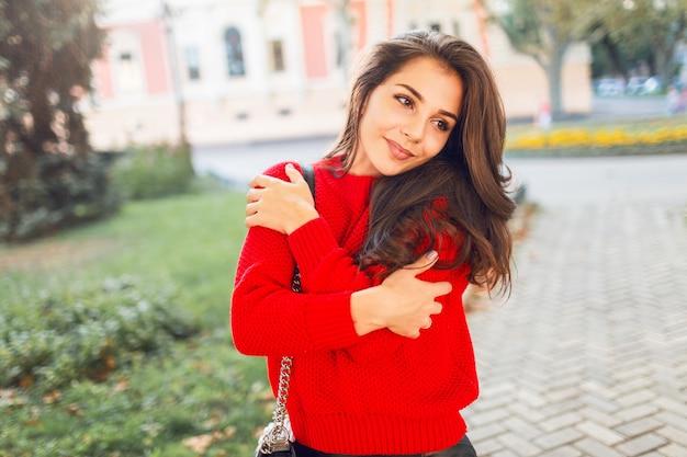 Zewnątrz portret uroczej uśmiechniętej kobiety w ciepły jesienny strój na co dzień spaceru w parku i ciesząc się słoneczną pogodą. romantyczny nastrój.