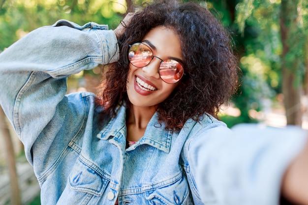 Zewnątrz portret uśmiechnięta czarna kobieta w różowych okularach