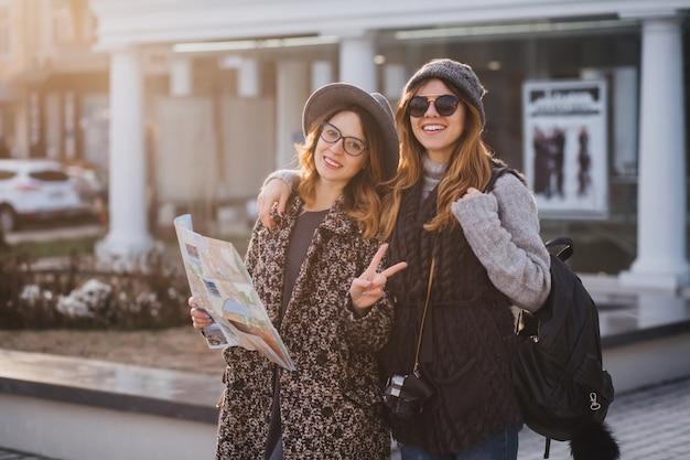Zewnątrz portret wesoła kobieta z czarnym plecakiem i aparatem obejmującym przyjaciółkę i uśmiechnięty. radosna młoda kobieta w eleganckim kapeluszu trzyma mapę miasta i robi znak pokoju śmiejąc się z siostrą.