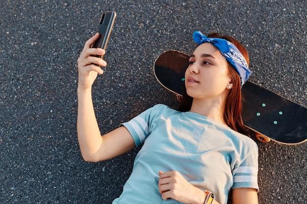 Zewnątrz strzał ciemnowłosej pięknej kobiety na sobie t shirt i opaska do włosów ustanawiające na drodze pośrodku ulicy, trzymając w rękach inteligentny telefon, biorąc selfie.