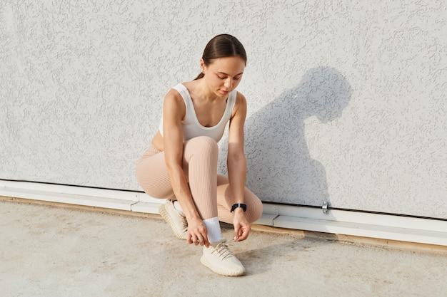 Zewnątrz strzał młoda kobieta biegacz wiązanie sznurowadeł, noszenie biały top i beżowe legginsy, robienie ćwiczeń sportowych na świeżym powietrzu, brunetka kobieta ćwicząca, trening, opieka zdrowotna.