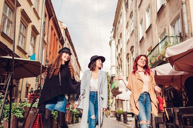 Zewnątrz strzał trzech młodych kobiet chodzących na ulicy miasta. szczęśliwe dziewczyny rozmawiają i bawią się