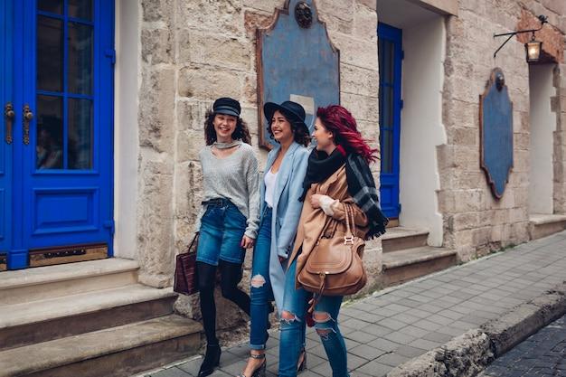 Zewnątrz strzał trzech młodych kobiet chodzących na ulicy miasta. szczęśliwe dziewczyny rozmawiają i dobrze się bawią