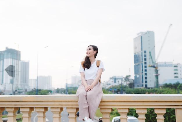 Zewnątrz styl życia z bliska portret szczęśliwa młoda kobieta w stylowym stroju dorywczo, siedząc na moście na ulicy. hipster ładna dziewczyna zabawy i korzystających z wakacji.