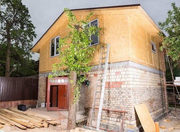 Zewnętrzna część częściowo wykończonego nowego domu, drabina i materiały budowlane ułożone na zewnątrz niedokończonego domu na placu budowy
