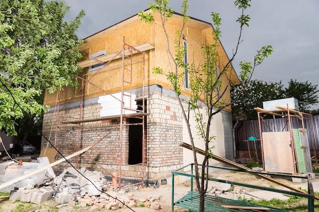 Zewnętrzna część częściowo wykończonego nowego domu, rusztowania i materiały budowlane ułożone na zewnątrz niedokończonego domu na placu budowy
