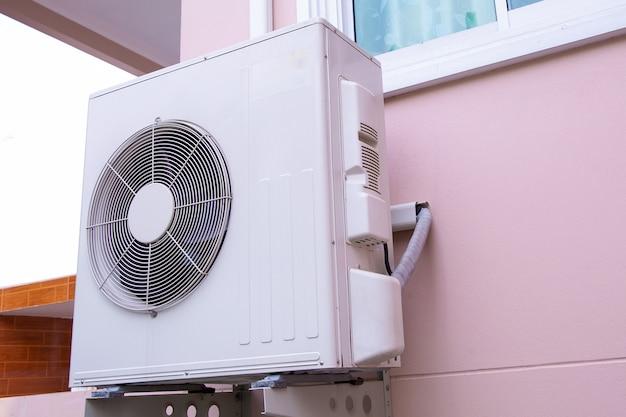 Zewnętrzna jednostka sprężarki klimatyzatora z dzieloną ścianą zainstalowana na zewnątrz budynku.